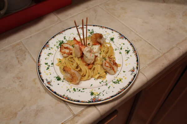 Seafood Pasta - Shrimp and scallops seared to perfection along with butter poached lobster in a white wine, garlic, tomato, and basil cream sauce over a nest of linquine noodles